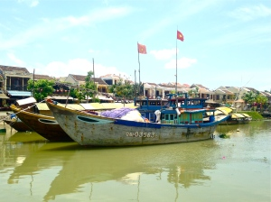 Vibrant boats float the Thu Bon river, a once flourishing trade route.